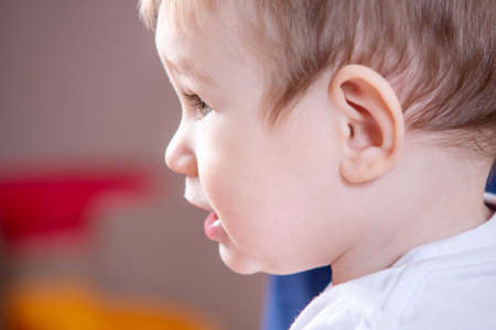 Portrait of cute little boy in profile. Baby seriously looks in the side close-up