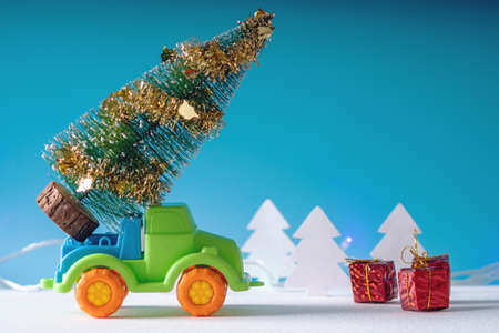 Toy car carries gifts in the Christmas and new years eve on a blue background. The concept of holiday shopping and discounts