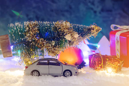 Toy car carries gifts in the Christmas and new year's eve on a blue background. The concept of holiday shopping and discounts