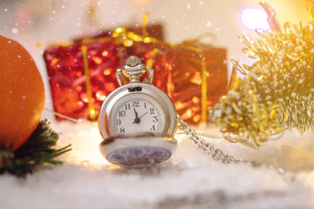 Pocket watch with a dial in the snow with gifts on the eve of holidays. Concept waiting for the magic of Christmas and new year Stock Photo