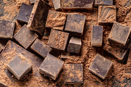Pieces of dark bitter chocolate with cocoa powder on dark wooden background. The concept of confectionery ingredients