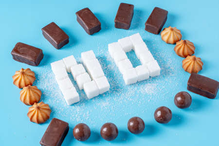 Text No is lined with sugar cubes with sweets and cookies. The concept of harm to the health of sweet and rejection of sucrose Фото со стока