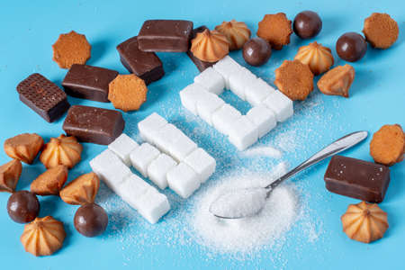 Text No is lined with sugar cubes with sweets and cookies. The concept of harm to the health of sweet and rejection of sucrose Stock Photo