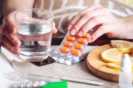 Thermometer pills water and lemon on tray. A person with a cold is treated in bed. Colds, flu and treatment Stock Photo
