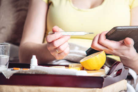 Thermometer pills water and lemon on tray. A person with a cold is treated in bed. Colds, flu and timely treatment Stock Photo