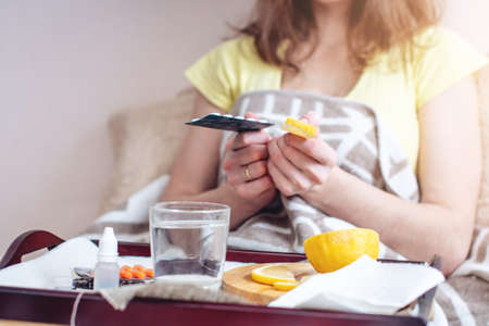 Woman with a cold chooses between pills and vitamins for treatment. Seasonal flu in winter Stock Photo