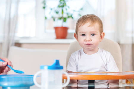 Mother feeding the baby holding out her hand with a spoon of porridge in the kitchen. Emotions of a child while eating healthy food. Stock Photo