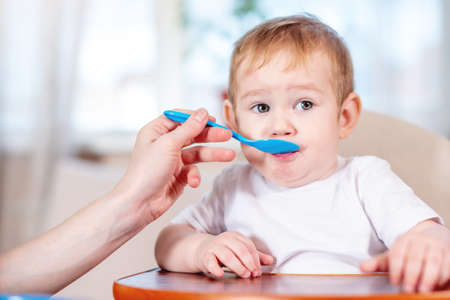 Mom feeding the baby holding out her hand with a spoon of food in the kitchen. Healthy baby food. The emotions of a child while eating Stock Photo