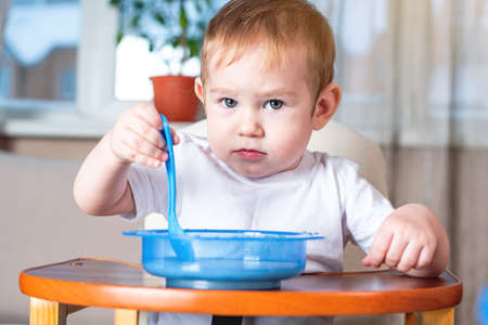 Little baby boy learning to eat with a spoon himself at the kids table in the kitchen. The concept of healthy baby food