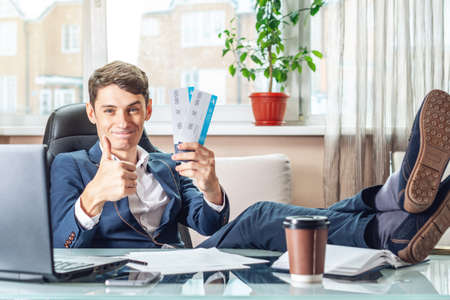 The young man is holding the won tickets. The joy of waiting for the journey. The concept of the office on vacation Stock Photo