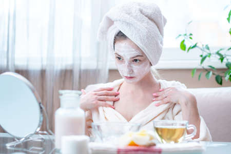 Beautiful happy young woman with cosmetic natural mask on her face looking at her skin. Concept skin care and Spa treatments at home 스톡 콘텐츠
