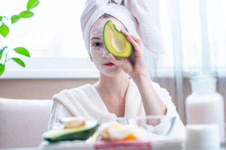 Beautiful happy young woman with cosmetic natural avocado mask on her face. Concept skin care and Spa treatments at home Archivio Fotografico - 116376286