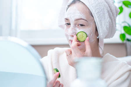Beautiful happy young woman with natural cosmetic mask and cucumber slices on her face. Concept skin care and Spa treatments at home Archivio Fotografico - 116376295