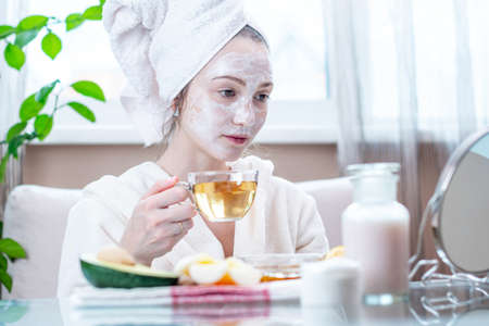 Beautiful happy young woman with natural cosmetic mask on her face. Concept skin care and Spa treatments at home