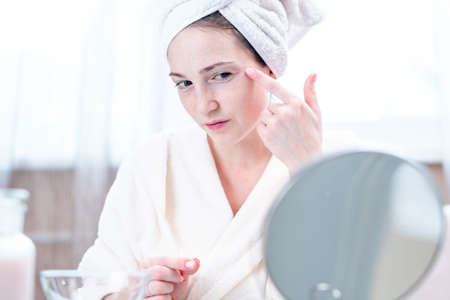 Beautiful happy young woman with a towel on her head looking at her skin in a mirror. The concept of timely hygiene and care for the skin at home