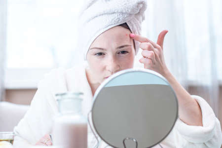 Beautiful unhappy young woman with a towel on her head looking at acne on her face. Concept of hygiene and care for the skin