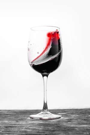Il vino rosso nel bicchiere schizza in azione su uno sfondo bianco. Biglietto dal design elegante