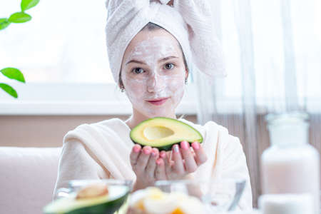 Beautiful happy young woman with cosmetic natural avocado mask on her face. Concept skin care and Spa treatments at home Archivio Fotografico - 116377268