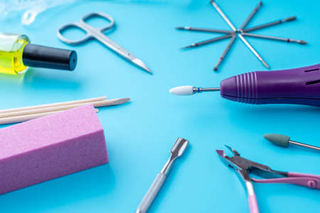 A set of cosmetic tools for professional manicure, nail care and to create beautiful designs on a blue background. Top view