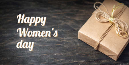 Holiday gift box Packed in crafting paper on dark wooden background. Holiday horizontal card Happy Women's day with text