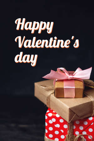 Holiday gift boxes Packed in crafting paper and red polka dots on dark wooden background. Vertical card Happy Valentine's day with text