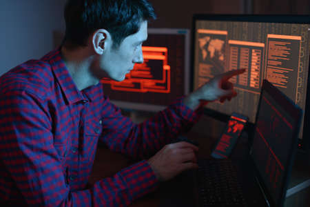 The male hacker in the hood is pointing his finger at the display indicating the location of the cyberattack and hacking data on the screen background in neon light. The concept of cyber security