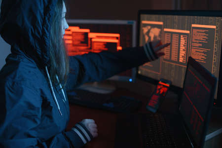 Girl hacker is pointing her finger at the display indicating the location of the cyberattack and hacking data on the screen background in the dark under neon light. The concept of cyber security