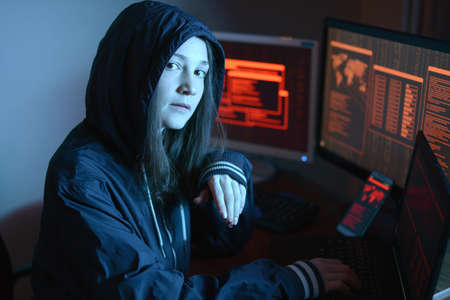 Girl in the hood looking in the camera. Hacker attacks and online fraud on the screen background in neon light. The concept of cyber security