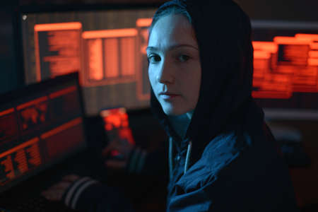 Girl in the hood looking in the camera. Hacker attacks and online fraud on the screen background in the dark. The concept of cyber security