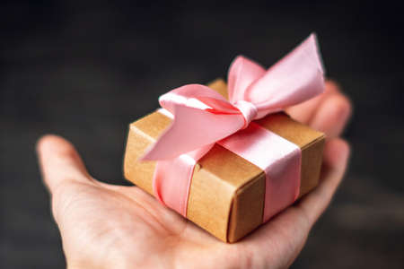 Hand holding Holiday gift box Packed in crafting paper with pink ribbon on dark wooden background. The concept of beautiful cards with gifts