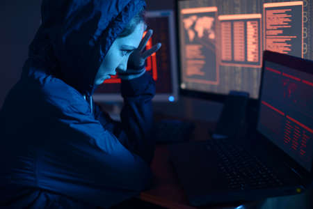 The hooded hacker girl is thinking about the problem of hacking or malware infection on the background of screens with codes in neon light. The concept of cybersecurity