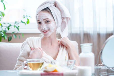 Beautiful happy young woman with cosmetic natural mask on her face looking at her skin. Concept skin care and Spa treatments at home Archivio Fotografico - 116560761
