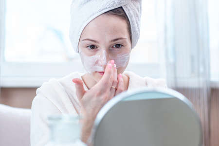 Beautiful happy young woman with a towel on her head applying cream of natural cosmetics on face moisturizing the skin. The concept of hygiene and care for the skin at home