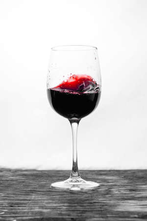 The red wine in the glass splashes in motion on a white background. Stylish design card