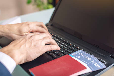 Man typing on the keyboard buying on the Internet airline tickets using a laptop. Purchasing and booking online