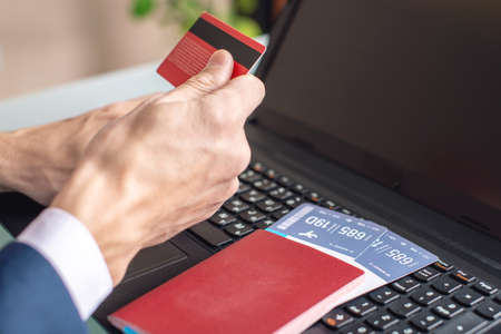 Man holding debit card in hand buying on the Internet airline tickets using a laptop. Purchasing and booking online