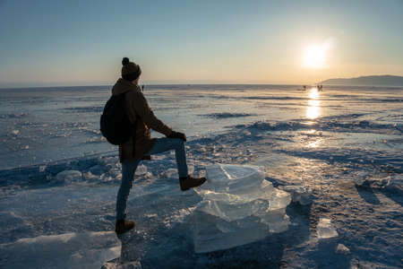 Man tourist traveler with a backpack watching the sunset on the snowy ice of lake Baikal. Concept of freedom and travel to the great places of nature