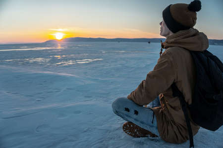 Man tourist traveler with backpack watching the sunset on the snowy ice of lake Baikal. The concept of freedom and travel to the great places of nature