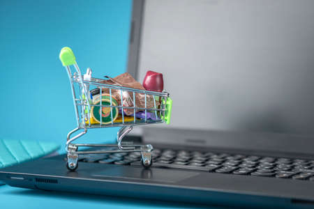 Daily purchases in the shopping cart on the laptop keyboard on a blue background. The concept of shopping in online stores
