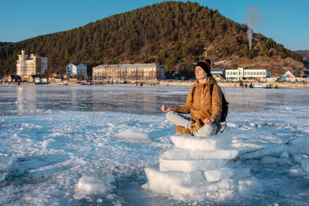 Man tourist with a backpack meditates sitting in Lotus position on the ice of lake Baikal. Calm and relaxation of the journey to nature