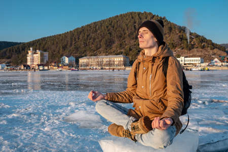 Tourist with a backpack meditates sitting in Lotus position on the ice of lake Baikal. Calm and relaxation of the journey to nature Stock Photo
