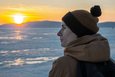 Tourist traveler with a backpack watching the sunset on the snowy ice of lake Baikal. The concept of freedom and travel to the great places of nature