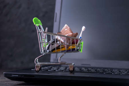 Daily purchases in the shopping cart on the laptop keyboard on a dark background. Concept of shopping in online stores Stock Photo