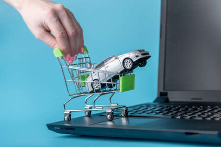Hand pushing shopping cart with car on laptop keyboard on blue background. The concept of online shopping vehicles on the Internet Archivio Fotografico
