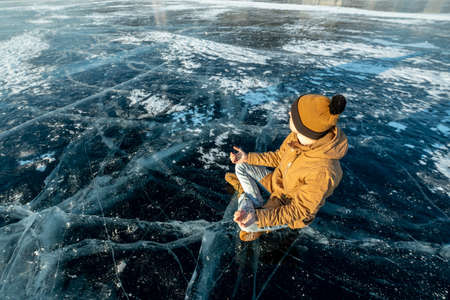 Tourist traveler meditates sitting in Lotus position on pure and transparent ice of lake Baikal. Travel to beautiful places of nature