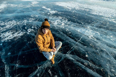 Tourist traveler meditates sitting in Lotus position on the ice of lake Baikal. Calm and relaxation of nature