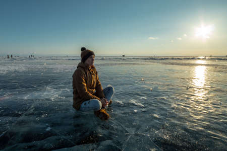 Man tourist with a backpack meditates sitting in Lotus position on the ice of lake Baikal at sunset. Calm, relaxation and freedom of nature