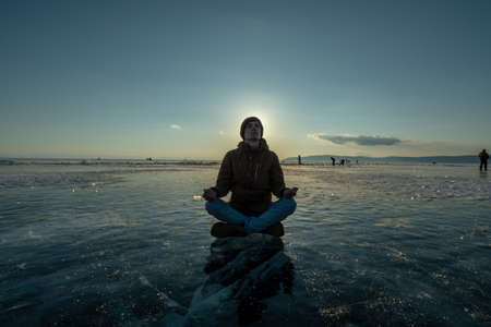 Man tourist with a backpack meditates sitting in Lotus position on the ice of lake Baikal at sunset. Relaxation and freedom of nature