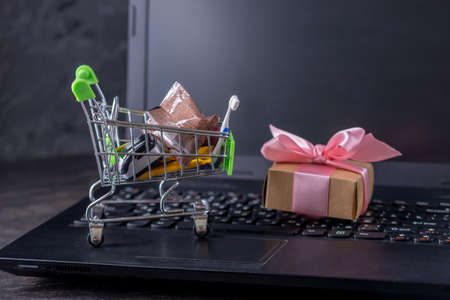 Daily purchases and gifts in the shopping cart on the laptop keyboard on a dark background. Concept of shopping in online stores