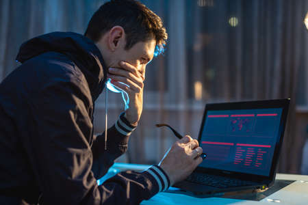 A young man with glasses working on a laptop at night. Freelancer designer or system administrator tries to solve the problem by staying late at work.